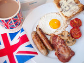 Bacon and eggs with cup of tea, toast and british flag — Stock Photo