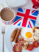 Full English breakfast with cup of tea, toast and british flag — Stock Photo