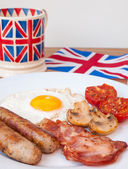 Bacon and eggs with cup of tea and british flag behind — Stock Photo