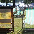 Two empty easy chairs in hyde park on a bright beautiful sunny day facing the serpentine river with other chairs and people in the background — Stock Photo