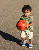 A Young Indian boy playing with a red ball in a green grass of a garden or a park — Stock Photo