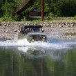 A jeep speeding along a  river — Stock Photo