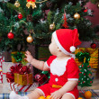 Baby in Santa costume near a Christmas tree — Stock Photo