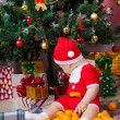 Stock Photo: Baby in Santcostume near Christmas tree