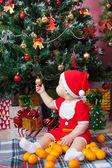 Baby in Santa costume near a Christmas tree — Stock Photo