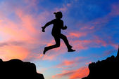 Silhouette of hiking woman jumping over the mountains at sunset — Stock Photo