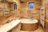 Bathroom in luxury home with bath and furniture — Stock Photo