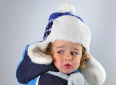 Happy little baby in a huge fur hat on white blackground — Stock Photo