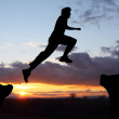 Silhouette of hiking man jumping over the mountains at sunset — Stock Photo