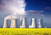 Nuclear power plant with yellow field and big blue clouds. — Stock Photo