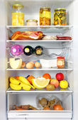 Fridge open full stocked loaded up with food and fresh ingredie — Stock Photo