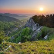 Stock Photo: Green Rocky moutain at sunset wih path and sun
