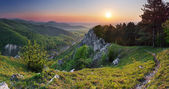 Green Rocky moutain at sunset wih path and sun — Stock Photo
