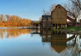 River reflection with watermill and tree — Stock Photo