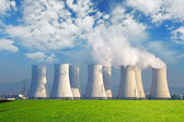 Nuclear power plant with yellow field and big blue clouds — Stock Photo
