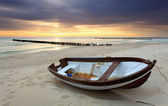 Boat on beautiful beach in sunrise — Stock Photo
