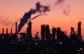 Oil refinery factory silhouette over sunset — Stock Photo