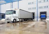Lossen grote container camions bij magazijn gebouw — Stockfoto
