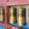 Row of buddhist prayer wheels in Gandan Monastery, Mongolia - Stock Photo