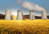 Nuclear power plant with yellow field and sun — Stock Photo