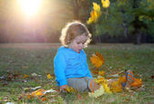 Cute little boy is playing with leaves in autumn park — Stock Photo