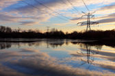 Electricity pylon with reflection in water at sunset — Stock Photo