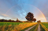 Rainbow over field road — Stock Photo