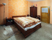 Orange Bedroom with a double wood bed — Stock Photo