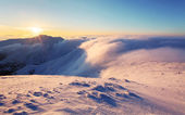 Winter sunset over the clouds with sun. — Stock Photo