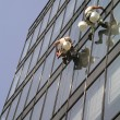 A man cleaning windows on a high rise building — Stock Photo