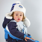 Happy little baby in a huge fur hat — Stock Photo