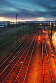 Railroad track at night with colorful sky — ストック写真