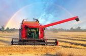 Harvester machine with rainbow — Stock Photo