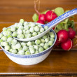 Frozen peas and fresh radish — Stock Photo