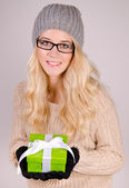 Winter girl holding a gift box. — Stock Photo