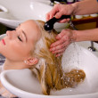 Hairdresser washing blond hair — Stock Photo