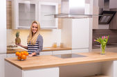 Young woman in modern kitchen — Stock Photo