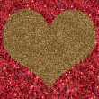 Photo: Golden heart on red background