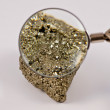 Looking through a magnifying glass on pyrite — Stock Photo