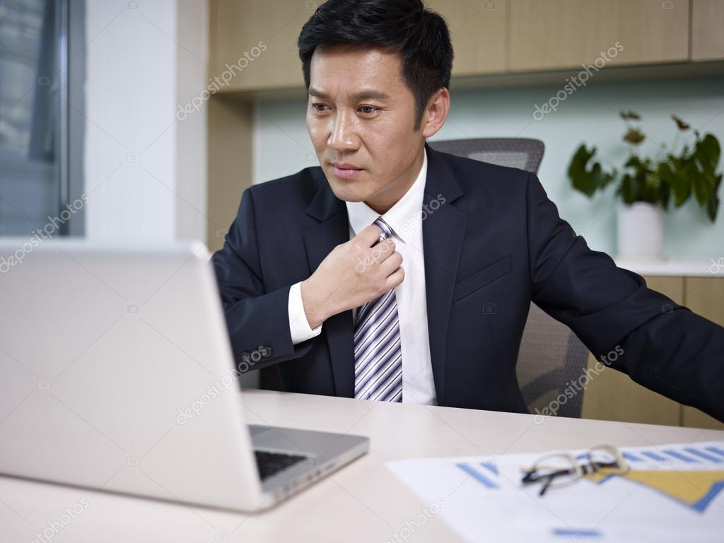 Asian businessman looking at laptop computer in office. — Stock Photo #17697349