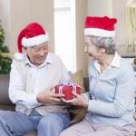 Senior Couple exchanging Christmas gifts — Stock Photo