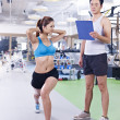 Young woman exercising in gym — Stock Photo