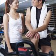 Man and woman talking in gym — Stock Photo