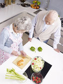 Senior couple chatting in kitchen — Stock Photo