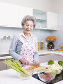 Senior woman preparing meal in kitchen — Stock Photo