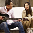 Young lovers playing guitar and singing — Stock Photo