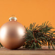 Gold ball on pine branch — Stock Photo