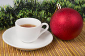 Red Christmas ball with cup of tea and festive decoration — Stock Photo