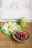 Spa and wellness setting with natural rosebuds, candle and towel. — Stock Photo