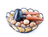A basket of walnuts and walnut open tools — Stock Photo